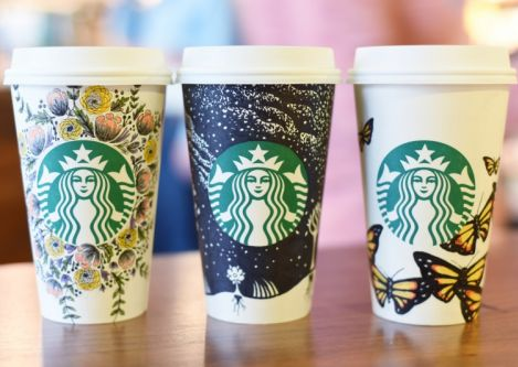 Photo showing a three Starbucks' cups with hand-drawn illustrations
