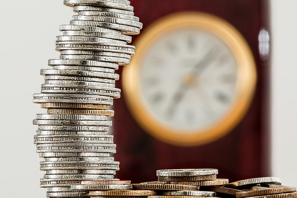 Photo with stacked coins and the clock in the background