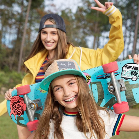 Teen girls in hats with skateboards in a park