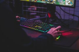 Man playing PC game on colorful keyboard and mouse